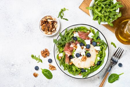 Green salad with arugula, spinach, pear, jamon, blueberries and feta cheese.Top view on white background. Healthy food, low calories dish.