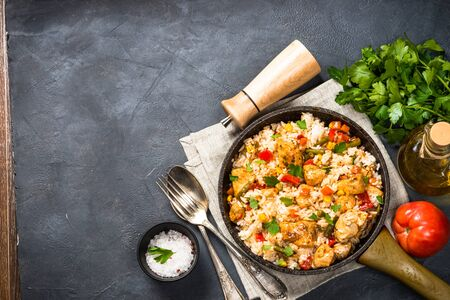 Rice with chicken and vegetables in skillet on black stone table. Top view with copy space.