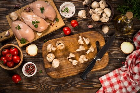 Chicken fillet with ingredients for cooking on dark wooden kitchen table. Top view with copy space. Stock fotó