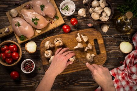Food cooling background. Chicken fillet, mushrooms and tomatoes with onion and spices on dark wooden kitchen table. Top view.