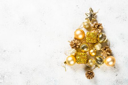 Christmas fir tree made from gold decorations on white.