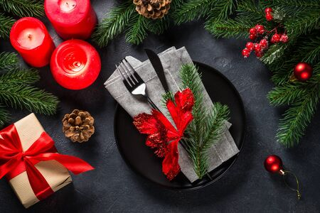 Christmas table setting on black top view.