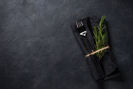 Black cutlery and napkin with a sprig of rosemary on black stone table top view. Foto de archivo - 134824461