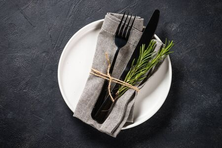 White plate, cutlery and napkin on black table top view. Foto de archivo - 134824469