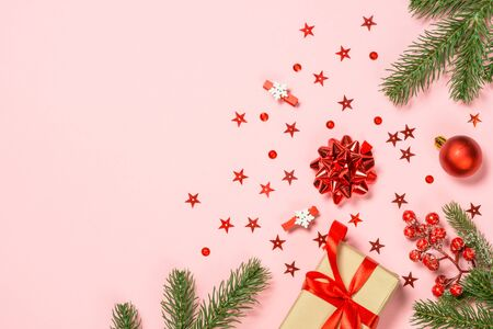 Christmas flat lay background on pink with holiday decorations.