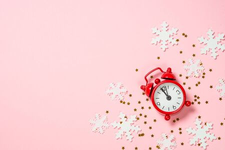 Christmas flat lay background with red clock and decor on pink. Reklamní fotografie