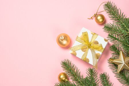 Golden Christmas flat lay background with present box and decorations on pink layout. Top view with copy space. Reklamní fotografie - 135503653