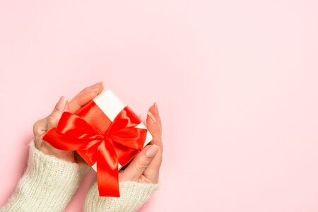 Christmas concept. Woman giving present box on pink background. Top view with copy space.