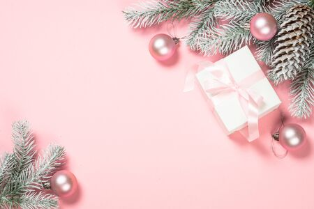Christmas pink flat lay background with christmas present box, fir tree and decorations on pink layout. Top view with copy space.