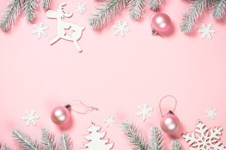 Christmas pink flat lay background with fir tree and decorations on pink layout. Top view with copy space.
