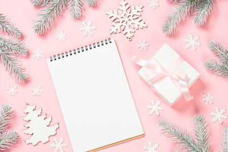 Christmas goals, plans, resolution. Flat lay background with christmas present box, decor and note book on pink layout. Top view with copy space. Reklamní fotografie