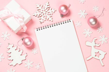 Christmas goals, plans, resolution. Flat lay background with christmas present box, decor and note book on pink layout. Top view with copy space. Banque d'images - 135503741