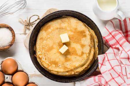 Crepes or thin pancakes in the frying pan with ingredients for cooking.