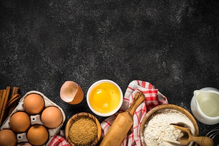 Baking background on black table. Flour, sugar, eggs, spices and utensil on black background top view with copy space.