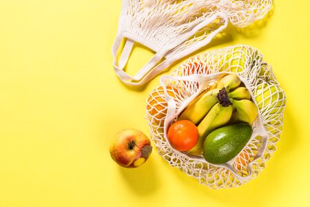 Mesh bag with fruits. Eco shopping concept, zero waste. Flat lay image on yellow background.