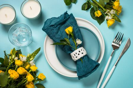 Spring table setting, served with blossom flower, white plate and cutlery on blue background. Flat lay image. Reklamní fotografie