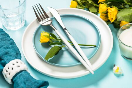 Spring table setting with flower on blue. Reklamní fotografie