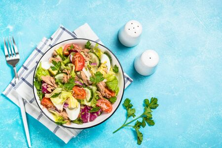 Tuna salad with green leaves, eggs and vegetables in white bowl. Top view at blue background. 스톡 콘텐츠