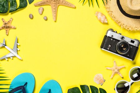 Summer travel flat lay background. Old film camera, hat, shell and palm leaves on yellow background. Standard-Bild