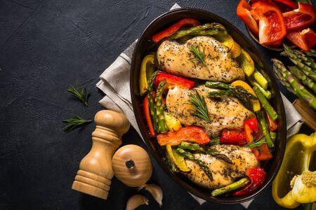 Gebackenes Hühnerfilet mit Gemüse. Gesundes Essen, Keto-Diät, Eintopfgericht. Draufsicht am dunklen Tisch. Standard-Bild