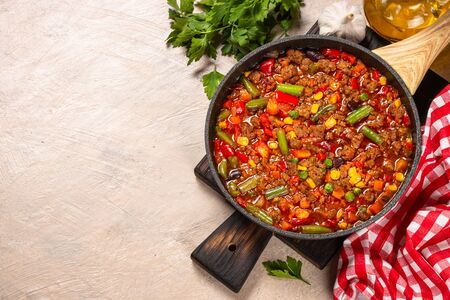 Chili con carne in skillet. Minced meat with vegetables. Traditional mexican food. Top view with copy space.