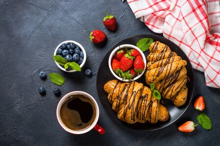 Croissant with fresh berries and coffee cup at black stone table top view. Traditional snack or breakfast.