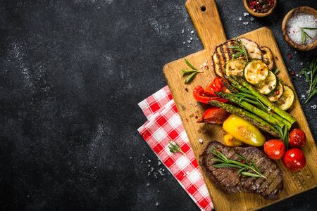 Beef steak grilled with vegetables on black stone table. Barbecue dish. Top view.