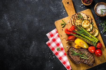 Steak de boeuf grillé aux légumes sur table en pierre noire. Plat de barbecue. Vue de dessus.