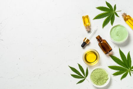 Cannabis oil and green leaves at white table.