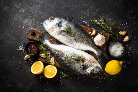 Fresh fish dorado on black stone table.