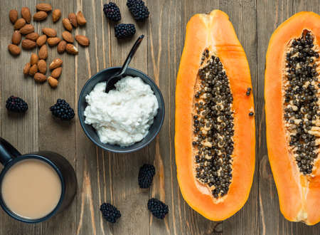 Breakfast on a wooden table: cottage cheese in a bowl, papaya halved,almonds and blackberries.