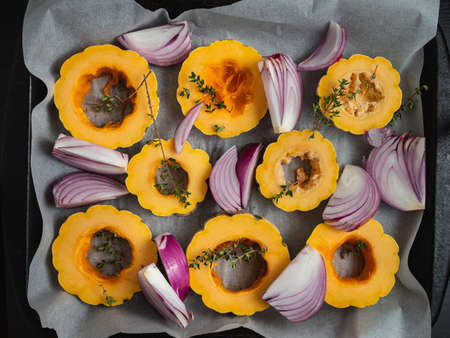 Slices of delicata squash and red onions on a baking sheet.