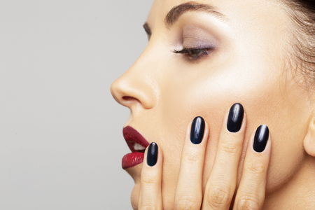 Beauty Portrait Woman close-up with perfect make-up. Beautiful Spa model Girl with Perfect Fresh Clean Skin and black nail polish. Youth and Skin Care Concept Stock Photo