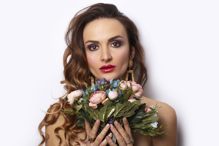 Glamour Sexy woman with bouquet of flowers. Beautiful brunette young model girl perfect holiday make-up, red seductive lips. Trendy makeup, beauty spa skin concept