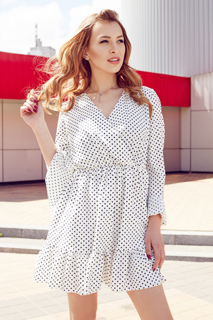 Young woman in white polka dots dress outdoor.