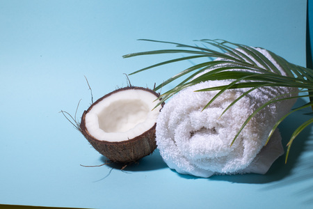 Spa still life of organic cosmetics with coconut on a light blue background, body care concept, Spa setting and health care items, towel, palm leaf Stock Photo