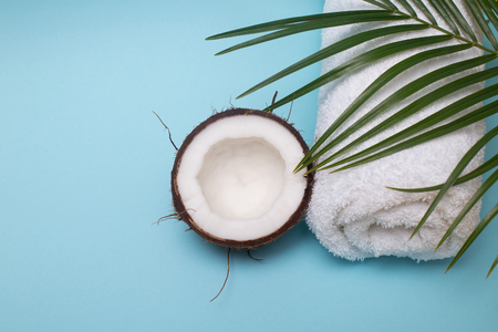 Spa still life of organic cosmetics with coconut on a light blue background, body care concept, Spa setting and health care items, towel, palm leaf, top view Foto de archivo