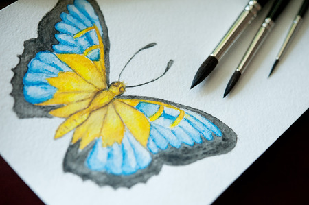 stationery needs: Set of colored watercolor pencils , brushes for painting and drawing butterflies on a wooden table
