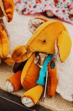 toy elephant: Beautiful yellow toy elephant in blue jacket Stock Photo