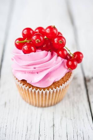 Cupcakes ( muffins ) with pink cream and red currant