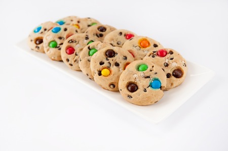 Beautiful cookies with multi-colored jelly beans on a white rectangular plate Фото со стока