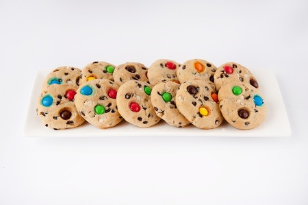 Beautiful cookies with multi-colored jelly beans on a white rectangular plate Stock Photo