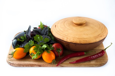 vegetables and beautiful pottery for baking on wooden board