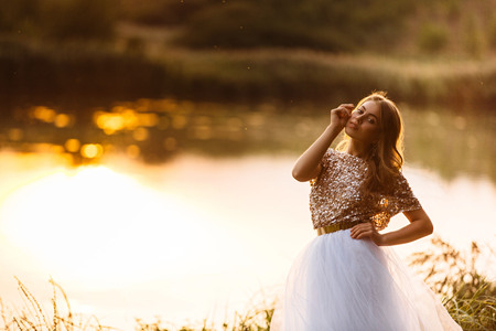 Portrait of a beautiful girl in a dress at sunset near a lake