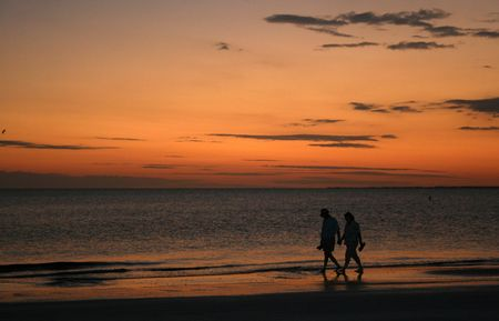 Couple strolling along the beach at sunset Stock Photo
