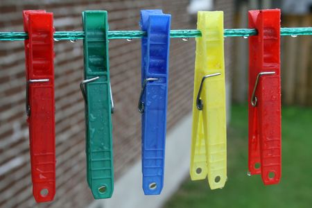 grasp: Clothespins in primary colors on a line  Stock Photo