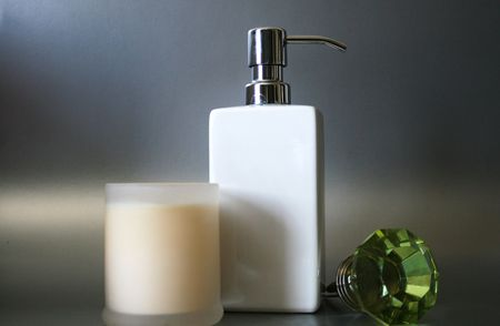 A Hand Soap Dispensor With Wine Stopper And Candle