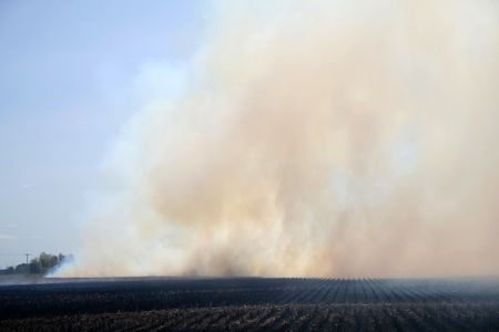Fire set to a farmers field creating smoke Stock Photo