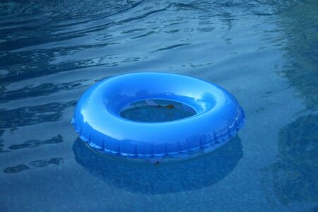 Blue inflateable tire floating in a pool