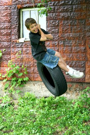 A boy is swinging on top of a tire